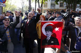 FILE - Relatives of detained military officers hold a portrait of Mustafa Kemal Ataturk, founder of modern Turkey, shouting slogans in front of a courthouse in Ankara, Oct. 9, 2013. On Thursday, Turkey's top appeals court overturned the officers' con