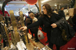 FILE - Shoppers look over items on sale at a Macy's store in New York.