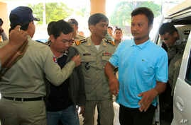 Chay Sarith, second left, and Mao Hoeun, second right in light blue shirt, suspected attackers who are accused of beating two opposition lawmakers along with another  man, are escorted by police officers at Phnom Penh Municipal Court in Phnom Penh, C