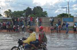 A group of people walk in a partially flooded street by the rains, while another persons try to walk over the water, holding a grating, in the Haitian capital Port-au-Prince, on May 2, 2017.