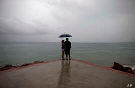 FILE - A couple looks out to sea as rainfall increases in Puerto Vallarta, Mexico.