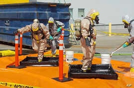 FILE - In this June 27, 2016 file photo provided by the Royal Canadian Mounted Police, members of the RCMP go through a decontamination procedure in Vancouver after intercepting a package containing approximately 1 kilogram (2.2 pounds) of the powerf