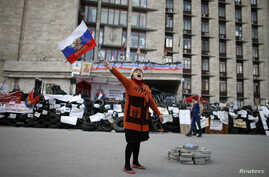 A pro-Russia protester shouts slogans as she waves a Russian flag outside a regional government building in Donetsk, in eastern Ukraine April 23, 2014.