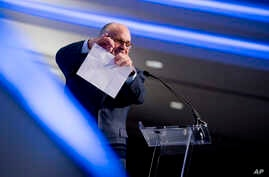 Rudy Giuliani, an attorney for President Donald Trump, pretends to tear a piece of paper as he speaks about the Iran nuclear agreement at the Iran Freedom Convention for Human Rights and Democracy at the Grand Hyatt, May 5, 2018, in Washington.