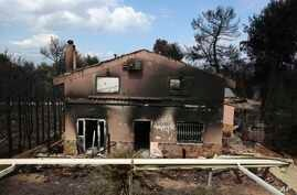 A burned house is seen in Agios Andreas, east of Athens, Tuesday, July 24, 2018.
