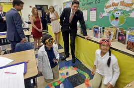 House Speaker Paul Ryan of Wis., right, and Rep. Carlos Curbelo, R-Fla., left, watch as students Christian Rubio, left foreground, and Jocelyn Zuniga, right foreground, explore the effect of friction on different surfaces, during a Science class at C
