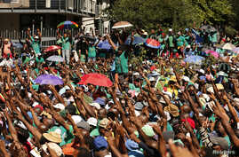 """Striking miners gather outside Lonmin's headquarters in Johannesburg, April 3, 2014. Platinum producer Lonmin has declared """"force majeure"""" with some contractors at its South African mines due to the effects of a lengthy strike, meaning a drop in busi"""