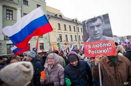 People march in memory of opposition leader Boris Nemtsov, portrait at right, in Moscow, Russia, Sunday, Feb. 26, 2017. Thousands of Russians take to the streets of downtown Moscow to mark two years since Nemtsov was gunned down outside the Kremlin. ...