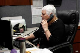 Joyce Endresen wears an Optune therapy device for brain cancer, as she speaks on a phone at work in Aurora, Illinois, March 29, 2017. She was diagnosed in December 2014 with Glioblastoma.