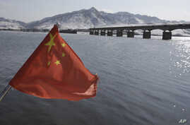 A Chinese flag is hoisted near the Hekou Bridge, right, linking China and North Korea, which was bombed in the 1950's during the Korean War, in Hekou, China on Feb. 7, 2013.