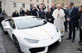 Pope Francis speaks with CEO of Lamborghini Stefano Domenicali next to a white Lamborghini donated to the pontiff by the luxury sports car maker, at the Vatican, Wednesday, Nov. 15, 2017.