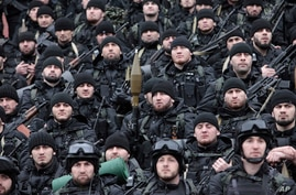 FILE - Chechen special forces listen to Chechnya's regional leader Ramzan Kadyrov (unseen) deliver a speech in Chechnya's capital of Grozny, Russia, Dec. 28, 2014.