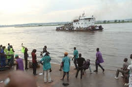 FILE - People that have been deported from Congo's capital Brazzaville, seen in background, arrive by river boat in Kinshasa, Democratic Republic of Congo, April 29, 2014.