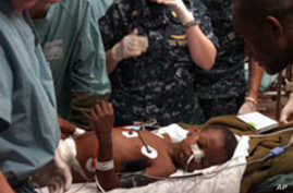 Medical professionals aboard the Military Sealift Command hospital ship USNS Comfort treat a six-year-old Haitian boy in the casualty receiving room aboard the 1,000-bed hospital ship, 19 Jan 2010