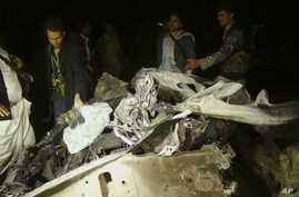 Shi'ite Houthi rebels stand next to a wreckage of a vehicle at the site of a car bomb attack in Sana'a, Yemen, June 17, 2015.