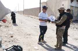 A man who identified himself as Omar Danoun, who claimed to be from Mosul, has his papers checked and is taken into custody by Iraqi soldier in Gogjali, Iraq, Nov. 12, 2016.