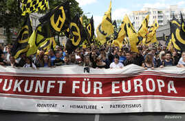 "FILE - Protestors carry a banner that reads: ""Future for Europe"" during a demonstration of the far-right Identitarian Movement (Identitaere Bewegung) in Berlin, June 17, 2017."