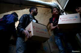 Men unload aid boxes from a Red Crescent aid convoy in the rebel held besieged town of Jesreen, in the eastern Damascus suburb of Ghouta, Syria, March 7, 2016.