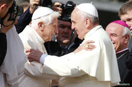 Pope Francis, right, greets Emeritus Pope Benedict XVI before a mass in Saint Peter's square at the Vatican, Sept. 28, 2014.