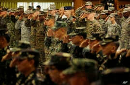 """U.S. and Philippine troops salute during the opening ceremony of their joint military exercise dubbed """"Balikatan 2015"""" at Camp Aguinaldo at suburban Quezon city, northeast of Manila, Philippines, April 20, 2015."""
