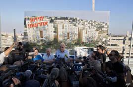 Israeli Minister of Housing and Construction Uri Ariel, center, speaks to journalists during a ceremony to mark the resumption of the construction of housing units in an east Jerusalem neighborhood, August 11, 2013.