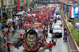 An effigy of Philippine President Rodrigo Duterte and U.S. President Donald Trump is seen while various activist groups march along a busy street during a protest against Duterte's plan to set up a Revolutionary Government, in metro Manila, Nov. 30,