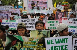 FILE - Rohingya refugees living in India hold placards during a protest in New Delhi demanding an end to the violence against ethnic Rohingyas in Rakhine state of Myanmar, March 11, 2015.