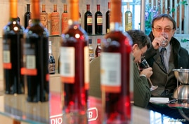(File) Visitors try Moldovan wine at an exhibition in Chisinau. Angered by Moldova's move toward the European Union, Russia banned all imports of Moldovan wines.