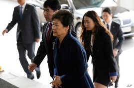 "South Korea's ousted leader Park Geun-hye, foreground, arrives at a prosecutor's office in Seoul, South Korea, March 21, 2017.  Park said she was ""sorry"" to the people as she arrived Tuesday at a prosecutors' office for questioning over a corruption"