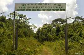 FILE - A sign marks the entrance of a former temple at a site deep in the Guyanese rainforest in Jonestown, Nov. 18, 2011.