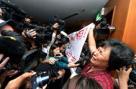 A Chinese relative of passengers aboard a missing Malaysia Airlines plane cries as she holds a banner in front of journalists reading 'We are against the Malaysian government for hiding the truth and delaying the rescue. Release our families uncondit