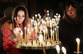 People light candles during a religious service at a church in Kyiv, Feb. 23, 2014.