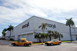 Taxi's pass by a Macy's department store, Jan. 5, 2017, in Doral, Fla.  The struggling department store said it will eliminate 10,000 jobs as it continues to close stores.