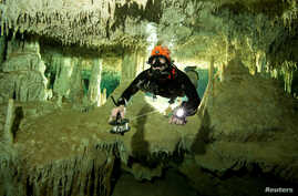 FILE - A scuba diver measures the length of Sac Aktun underwater cave system as part of the Gran Acuifero Maya Project near Tulum, in Quintana Roo state, Mexico, Jan. 24, 2014. Herbert Mayrl/Courtesy Gran Acuifero Maya Project (GAM) handout.