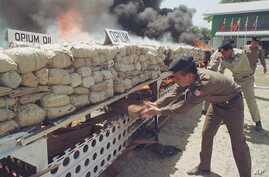 Burmese narcotic control officials put more wood to burn some six tons of seized opium, heroin and other drugs before diplomats, journalists and international business leaders in Rangoon, Burma. (File Photo)