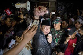 A protester raises his fist during an anti-communism rally outside the office of Legal Aid Institute early Sept. 18, 2017. A mob opposed to public discussion of Indonesia's 1965 massacre of communists tried to force its way into the building where th