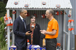 President Barack Obama, left, looks at a solar powered lamp during a tour of the Power Africa Innovation Fair, July 25, 2015, in Nairobi.