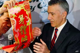 U.S. Ambassador to the Philippines Philip Goldberg, right, is presented a Chinese New Year scroll by journalist Wilson Flores during a forum Wednesday, Feb. 3, 2016 at suburban Quezon city, northeast of Manila, Philippines.