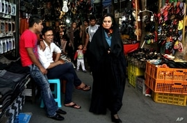 Iranian woman makes her way through bustling bazaar in downtown Tehran, May 28, 2013.