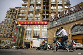 FILE - A delivery cart and cyclist ride past a building housing the Fengrui law firm in Beijing.