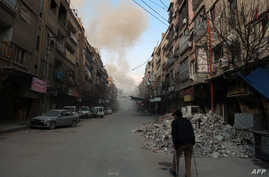 FILE - A Syrian man on crutches walks down a street as smoke billows in the rebel-held town of Douma, in the besieged Eastern Ghouta region on the outskirts of the capital Damascus, following air strikes by regime forces on the area on Feb. 23, 2018.
