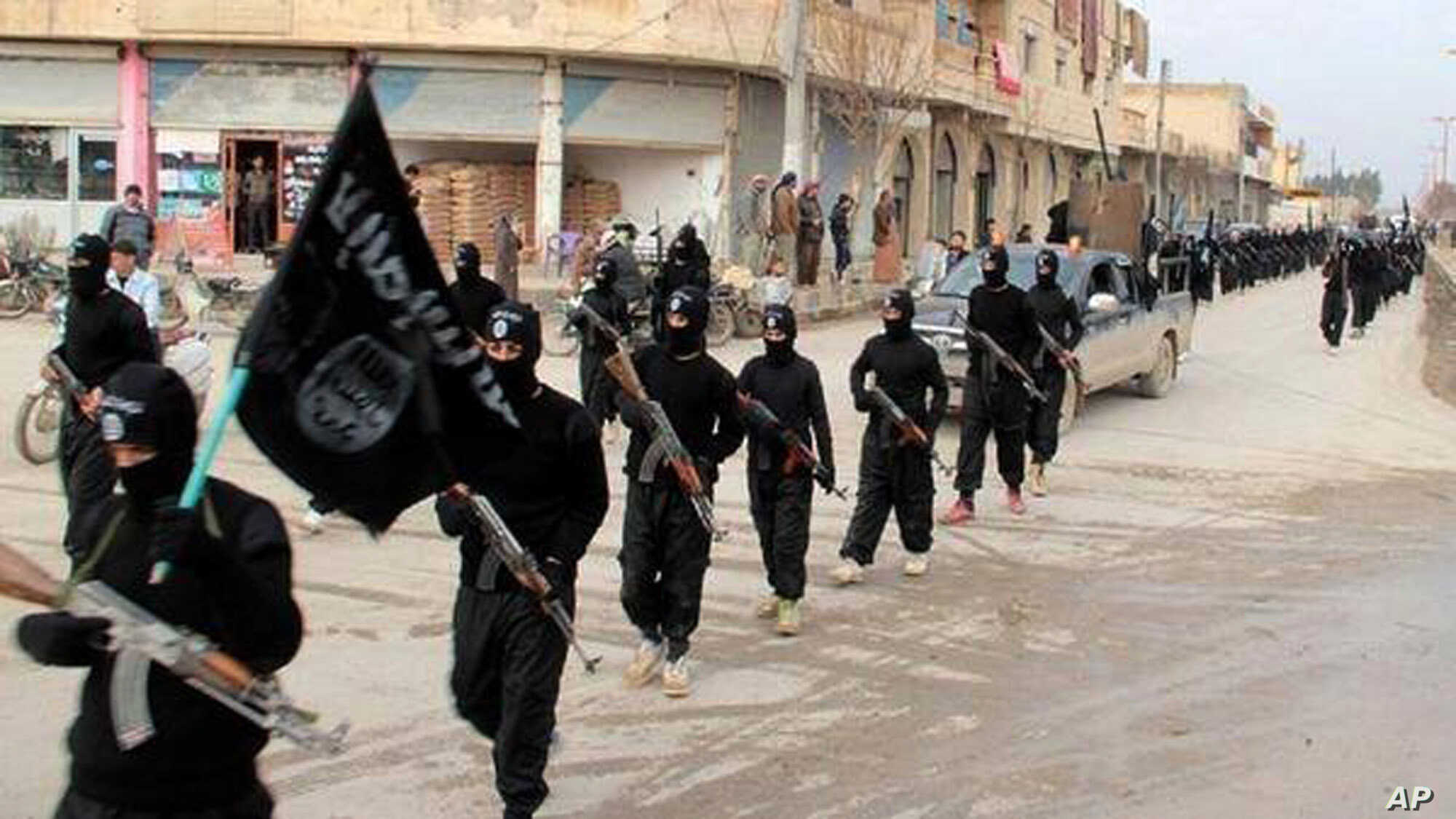 FILE - undated image posted on a militant website shows fighters from the al-Qaida linked Islamic State of Iraq and the Levant (ISIL) marching in Raqqa, Syria.