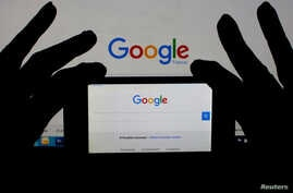 A smartphone and computer screen display the Google home page. U.S. presidential elections typically spur online searches for information about moving to Canada.