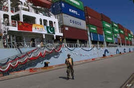 A Pakistan Navy soldier stands guard while a loaded Chinese ship prepares to depart, at Gwadar port, about 700 kilometers (435 miles) west of Karachi, Pakistan,  Nov. 13, 2016.