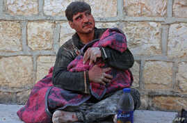 A Syrian man weeps as he cradles the body of his daughter who was killed following reported shelling in the town of Khan Sheikhun in the southern countryside of the rebel-held Idlib province, on February 26, 2019.