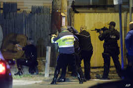 Police officers aim their weapons Friday evening, April 19, 2013, in Watertown, Massachusetts.