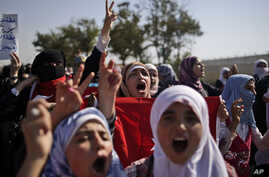 Syrians, who fled their homes due to fighting between the Syrian army and the rebels, shout slogans as they march toward the Turkish side of the border, August 28, 2012