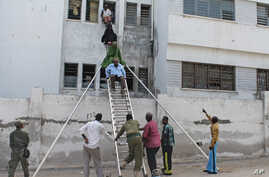 Survivors are helped to escape from a window at Mogadishu'