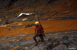 A rescue worker searches for victims at Bento Rodrigues district that was covered with mud after a dam owned by Vale SA and BHP Billiton Ltd burst, in Mariana, Brazil, Nov. 8, 2015.