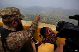 A Pakistan army officer points out the Indian forward area posts to journalists at Bagsar post on the Line of Control that divides Kashmir between Pakistan and India, on October 1, 2016. According to a report, Prime Minister Nawaz Sharif urged spy ch